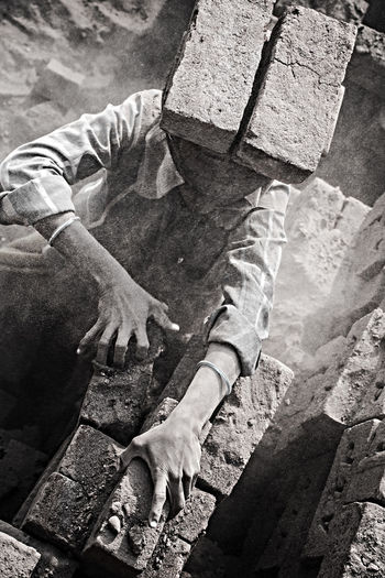 High angle view of manual worker carrying bricks at construction site