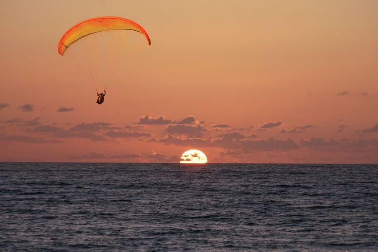 Orange sunset Sky Sea Sunset Water Horizon Over Water Extreme Sports Parachute Beauty In Nature Orange Color Adventure Cloud - Sky Horizon Transportation Mid-air Scenics - Nature Joy Parasailing Paragliding Sport Nature