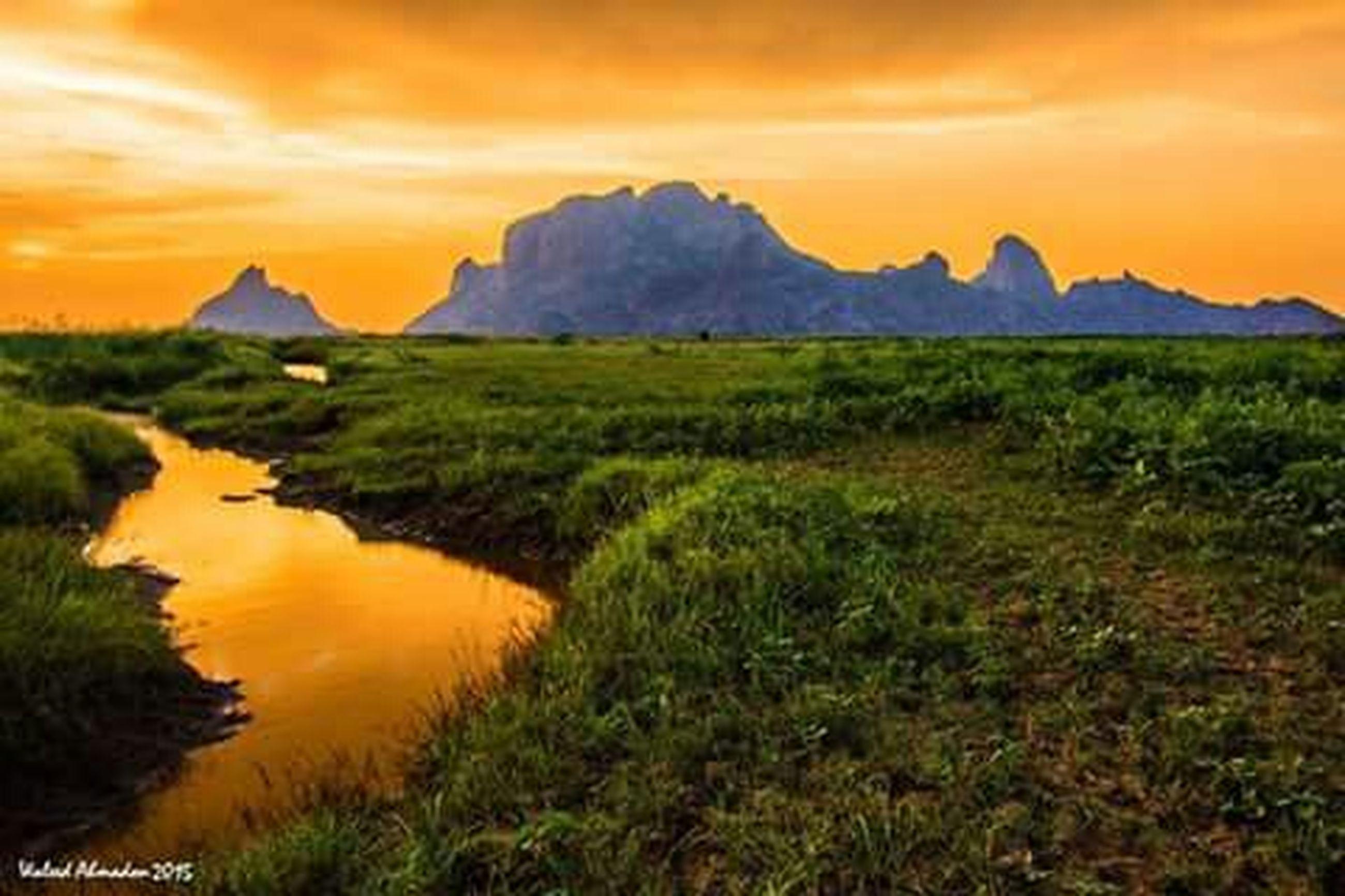 sunset, tranquil scene, scenics, tranquility, beauty in nature, mountain, sky, landscape, orange color, nature, idyllic, grass, mountain range, cloud - sky, non-urban scene, water, majestic, cloud, remote, dramatic sky