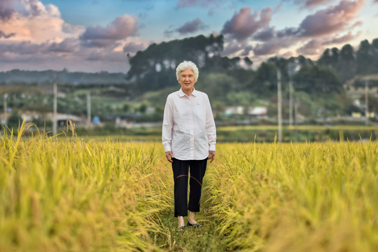 Portrait of smiling old woman standing on field