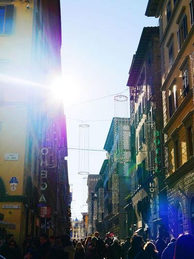 Crowd on illuminated city against clear sky