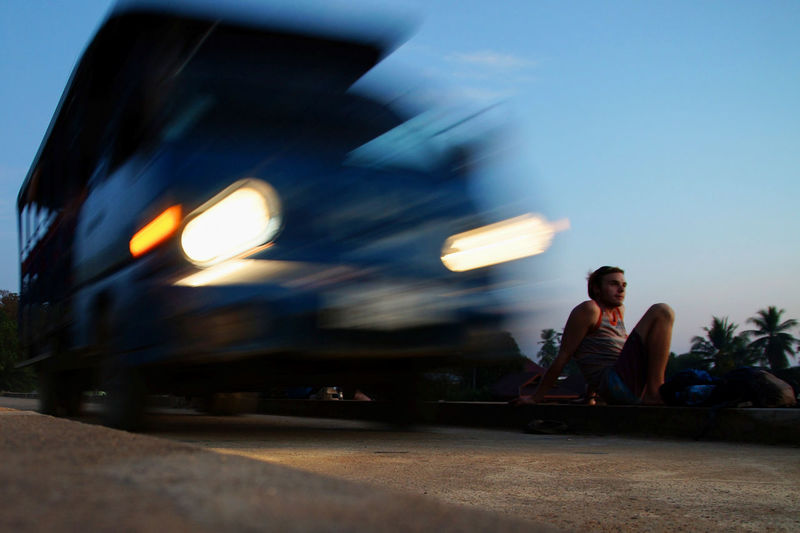 Blurred motion of vehicle moving on road by man during sunset