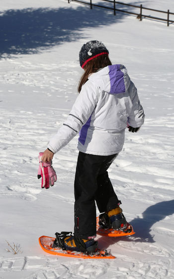 little girl tries to snow on the soft white snow Babe Snowshoe Child Clothing Cold Temperature Day Full Length Girl Leisure Activity Lifestyles Nature Outdoors People Playing Real People Recreational Pursuit Snow Snowshoe Trip Snowshoeing Snowshoes Sport Warm Clothing White Color Winter Winter Sport