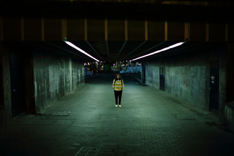 Woman In Illuminated Underground Walkway