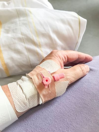 Cropped Hand Of Person With Bandages On Bed