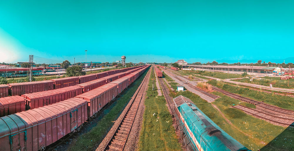 High angle view of freight trains at shunting yard against clear blue sky