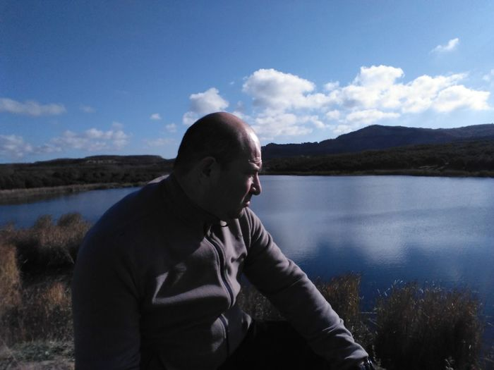 Thoughtful mature man sitting at lakeshore against blue sky