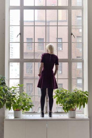 Rear view of woman standing on window sill
