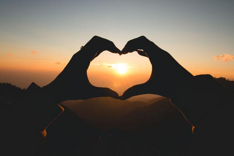Fingers forming heart shape at dusk