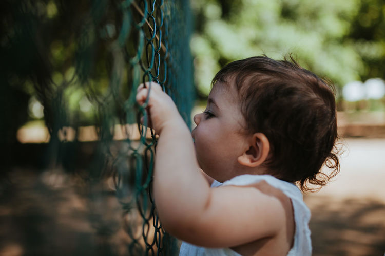 Side view of cute baby girl looking through fence