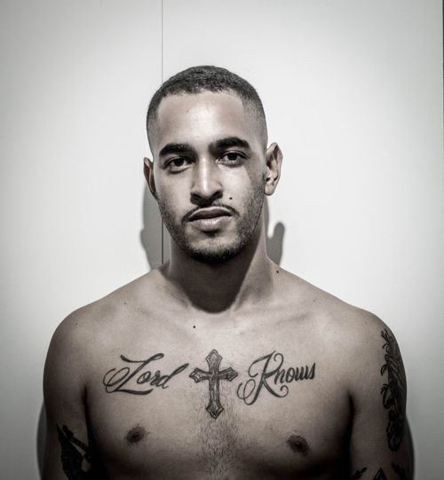 Portrait Of Young Man With Tattoos While Standing Against Wall