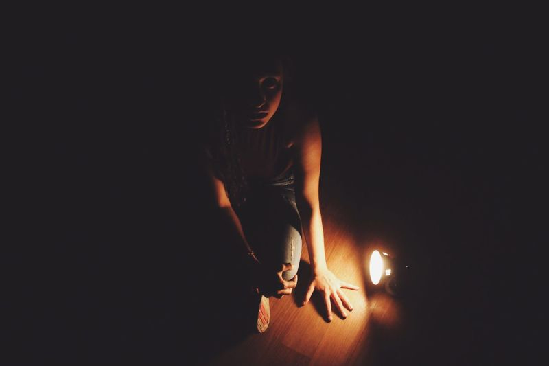 High angle portrait of young woman sitting by illuminated flashlight on floorboard