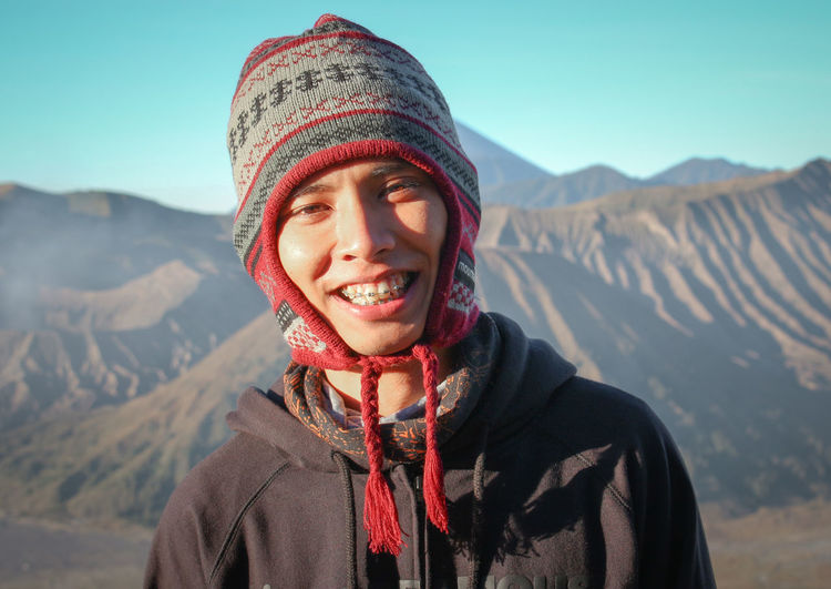 Portrait of smiling man in knit hat against mountains