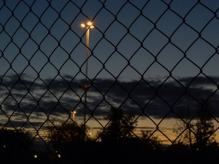 Close-up of illuminated chainlink fence against sky during sunset