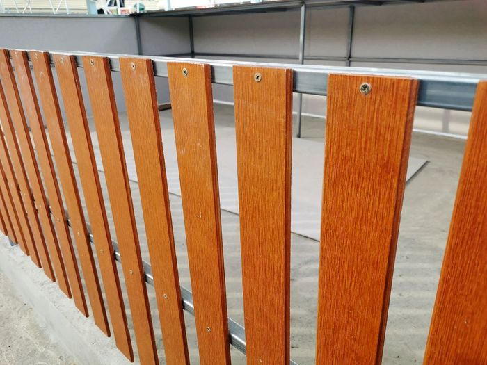 Close-up of wooden railing by fence