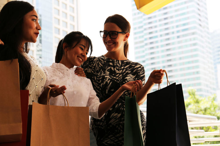 Women holding shopping bags while standing outdoors