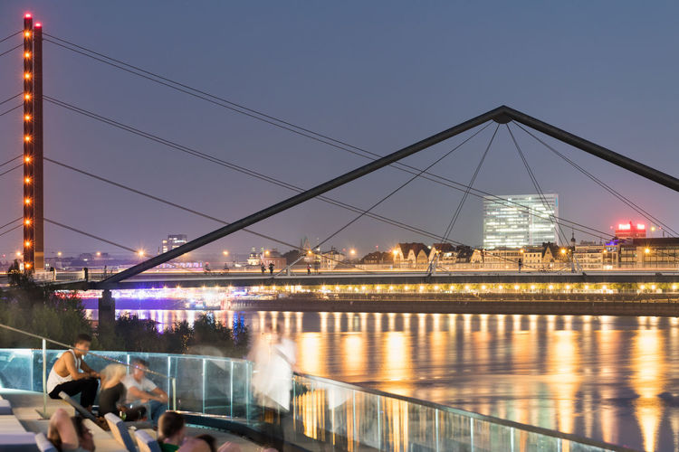 DUESSELDORF, GERMANY - SEPTEMBER 14, 2016: Unidentified visitors enjoy the spectecular sunset over the Rhine promenade. Architecture Attraction Bridge - Man Made Structure City Dusk Düsseldorf Germany Illuminated M Medienhafen New Media Harbor Night People Place To Be  Reflection River Scenics Ship Tourism Transportation Travel Travel Destinations Urban Urban Geometry Water