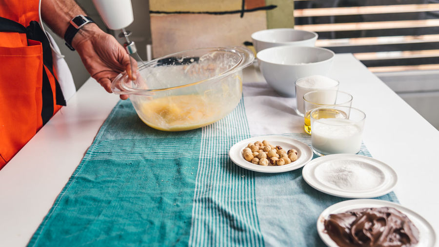 Cropped image of man mixing eggs in bowl at table in kitchen