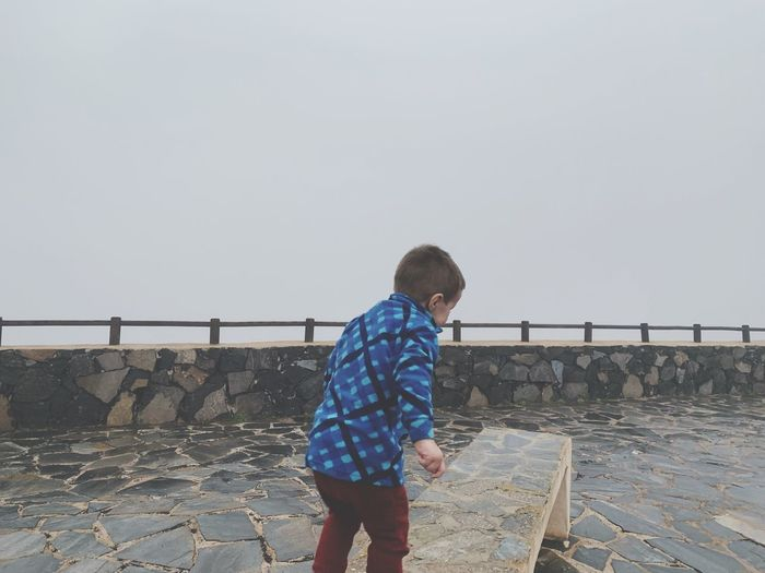 Side view of boy standing on footpath against sky during foggy weather