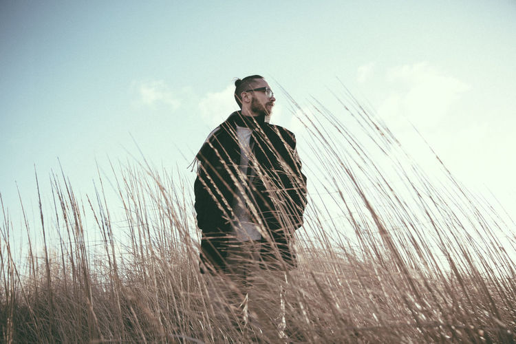 Fashionable adult male gazing into the distance standing in golden tall grass