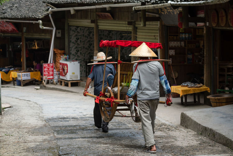 Travel Photography Architecture Asian Style Conical Hat Building Exterior Built Structure Day Full Length Mammal Men Occupation Outdoors Pointy Hat Real People Rear View Tourism Tourist Destination Walking Working The Traveler - 2018 EyeEm Awards The Street Photographer - 2018 EyeEm Awards The Photojournalist - 2018 EyeEm Awards Summer Road Tripping