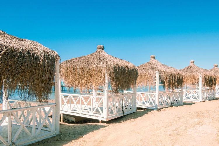 Built structure on beach against clear blue sky