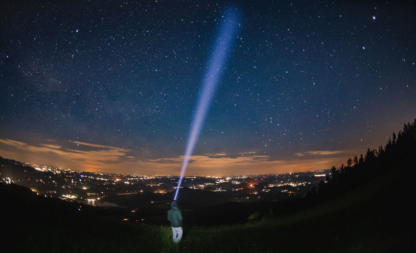 Rear view of person with flashlight on mountain against star field