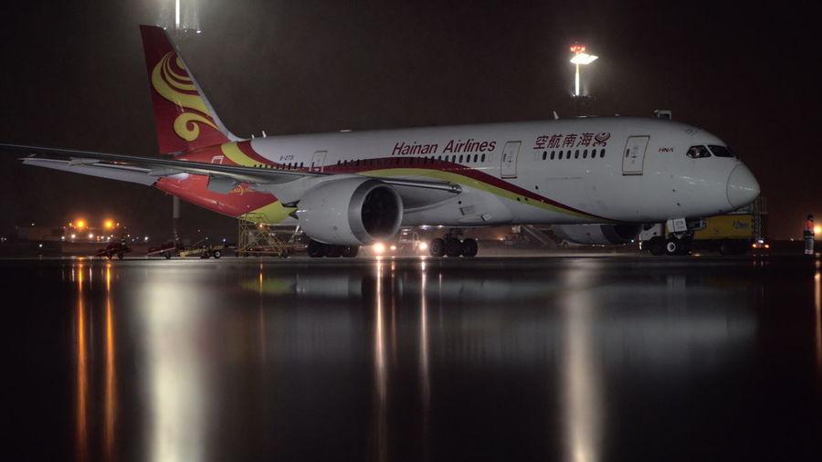 Illuminated airplane at airport runway at night