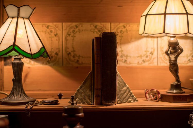 Close-Up Of Illuminated Electric Lamps And Old Books On Sideboard At Home