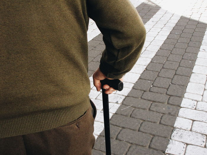 Rear view of man standing with walking cane on street