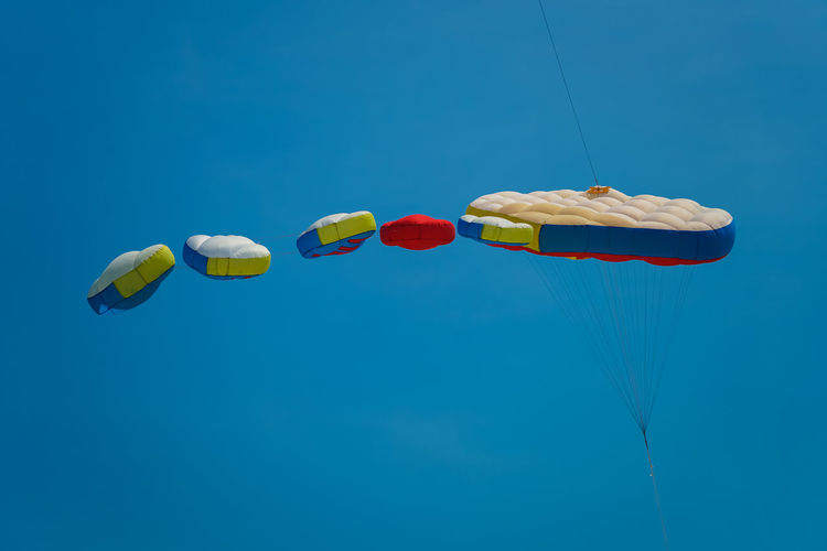 Low angle view of parachutes flying against blue sky