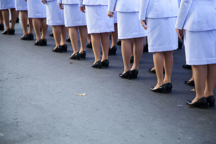 Low Section Of Women Wearing White Uniform Standing On Road