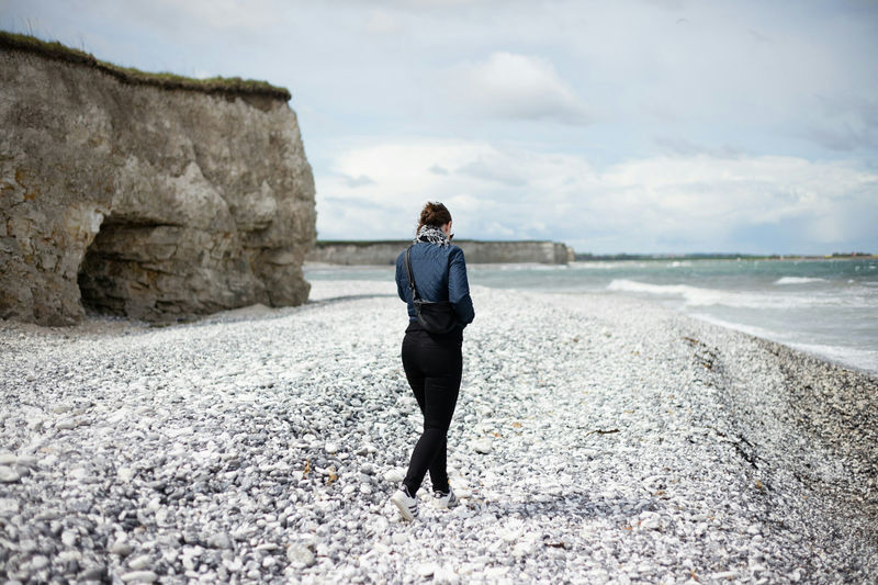 Rear View Of Woman Walking On Pebbles At Beach By Cliffs Of Sangstrup Against Sky