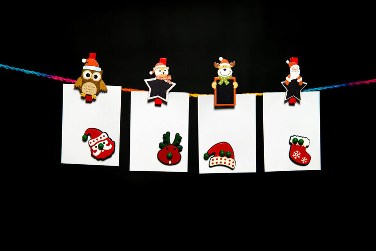 Hanging white paper sheet on colorful rope with Christmas theme paper clip and Christmas decoration Black Background Christmas Holiday Reindeer Santa Season Greetings Blank Paper Close-up Day Human Representation Indoors  No People Note Paper Clip Studio Shot