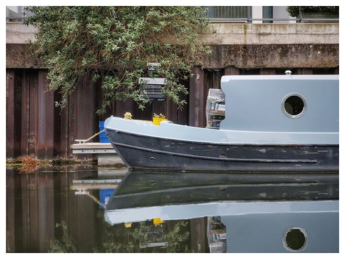 Boat moored by lake against building