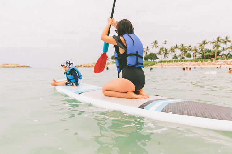 Woman With Baby Boy On Paddleboard In Sea Against Sky