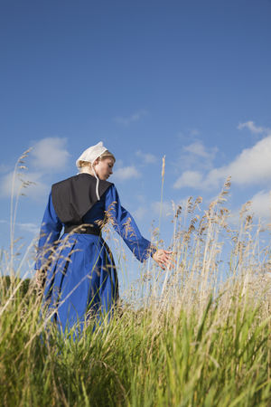 Amish woman in blue dress and black cape in a field Afternoon Amish Amish Country Apron Black Blonde Blue Bonnet Cape  Dress Field Girl Grass Low Angle View Pensive Religion Religious Beliefs Serious Sky And Clouds Sunlight Sunlight ☀ Walking Woman