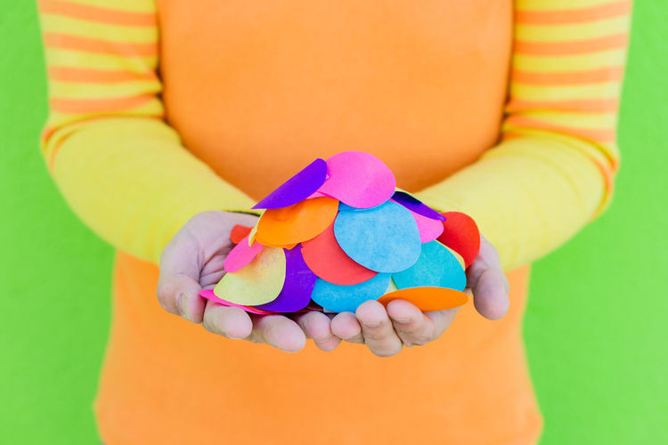 Close-up of hand holding multi colored candies