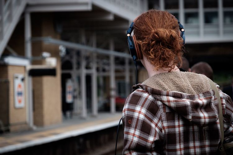 Rear View Of Woman With Curly Hair Using Headphones