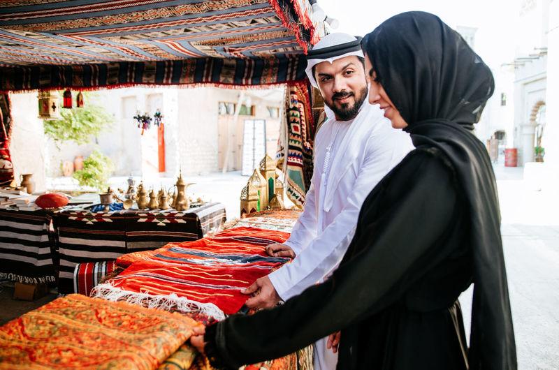 Couple buying clothing at market