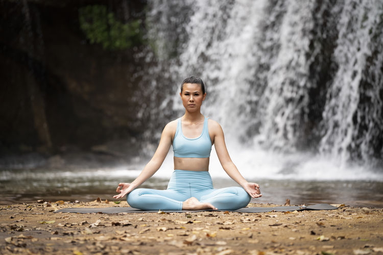 Full length of woman meditating against waterfall