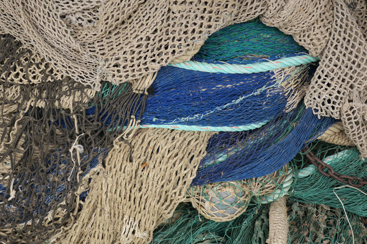 fishing nets with float and chain Backgrounds Blue Close-up Commercial Fishing Net Complexity Day Fishing Fishing Industry Fishing Net Full Frame High Angle View Multi Colored No People Pattern Rope Softness Still Life Strength Textile Textured  Tied Up