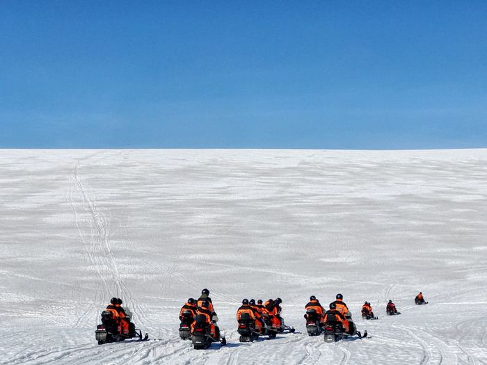People On Snow Covered Landscape Against Blue Sky