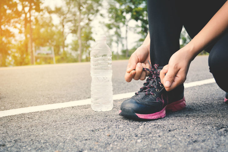 Low Section Of Woman Tying Shoelace While Kneeling By Bottle On Road