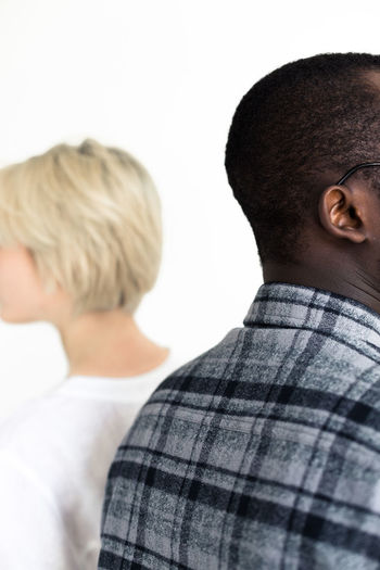 To listen vs to hear. Casual Clothing Couple Couple - Relationship Headshot Interracial Love Love Men People Real People Rear View Relationship Studio Shot Togetherness Two People White Background Women Young Adult Young Women