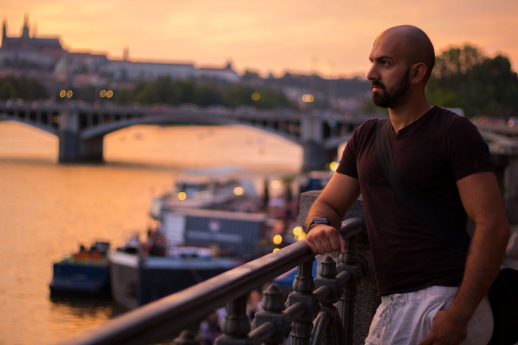 Thoughtful Bald Man Standing By Railing In City During Sunset