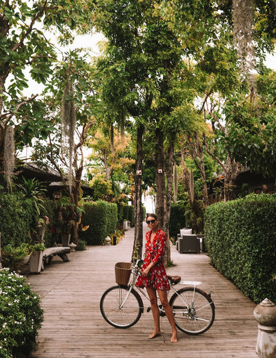Woman in garden with bicycle in Ko Samui Plant One Person Bicycle Transportation Full Length Real People Lifestyles Day Casual Clothing Young Adult Leisure Activity Looking At Camera Outdoors Riding Bike Thailand Ko Samui Resort Woman Girl Fashion Lifestyle Dress Model Garden