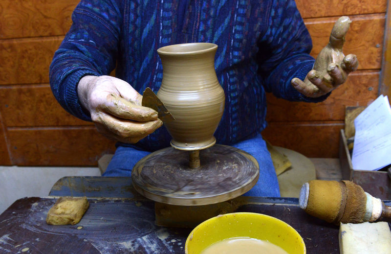 Craftsperson Shaping Pot On Pottery Wheel