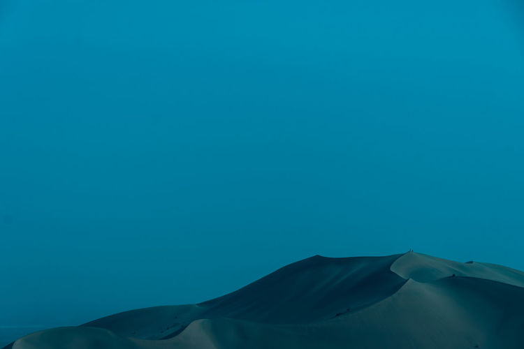 Low angle view of sand dunes in desert against clear blue sky