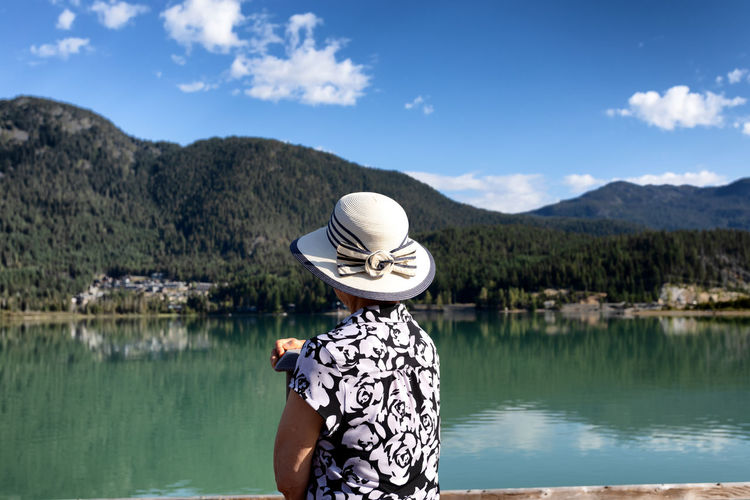 Woman in hat by lake against sky